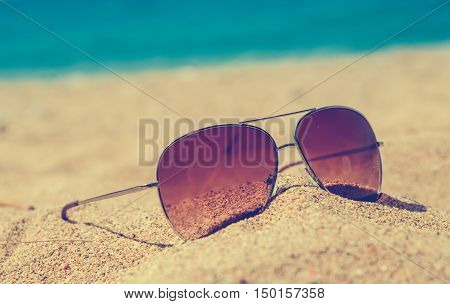 poster of blurred abstract Fashion sunglass on the summer beach at ocean background vintage filter Summer vacation actually relaxing summer concept vocation time summer background