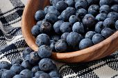 Freshly washed blueberries spilling out of a wooden bowl onto a handwoven dish towel.  Close-up with
