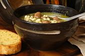 Traditional Italian wedding soup in rustic stoneware bowl with toasted garlic bread.  Close-up with shallow dof.