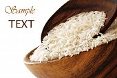 Uncooked rice in wooden bowl with spoon on white background with copy space.  Macro with shallow dof