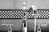 Shiny new stainless steel Victorian styled faucet with ceramic tile backsplash.  Black and white clo