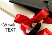 Diploma with red ribbon and black graduation cap on white background with copy space.  Macro with sh