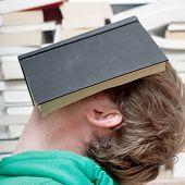 A man sleeping behind a book