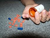 pic of drug addict  - pills spill across the floor from the hand of a young woman - JPG
