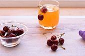Fresh Red Delicious Cherry And Fresh Squeezed Orange Juice On Wooden Background. Fresh Ripe Cherries poster
