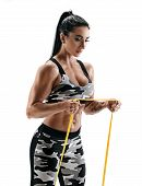 Beautiful Strong Model Performs Exercises Using A Resistance Band. Photo Of Latin Woman In Military  poster