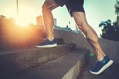Sport Hard. Close Up Of Male Feet Climbing Stairs Outside. Well Shaped Man Is Jogging At Dawn poster