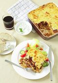 pic of greek food  - Pastitsio Greek taverna type meal with tzatziki fresh bread and a tumbler of red wine - JPG