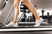 Close Up Girls Legs Walking At The Treadmill In The Gym Over Sunrise. Wearing In White Orange Blue S poster