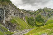 Mountain Landscape With Many Waterfalls In The Swiss Alps Under An Overcast Sky poster