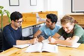 Three Students Studying And Doing Homework Together. Young Men Talking, Writing And Sitting At Desk  poster