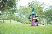 Side View Of Young Fit Asian Women In One Legged Bridge Pose, Female Base Lying On Grass And Support poster