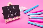 Small Blackboard With Back To School Words And School Supplies Of Bright Pink And Blue Colors On A P poster