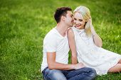 The Lovely Beautiful Couple In Love Sitting On Green Grass. Romantic Love Story In The Park. Young G poster