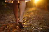 stock photo of dirt road  - Young female legs walking towards the sunset on a dirt road