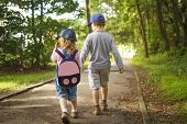 Little Friends Children Hold Hands And Walk Along Path In Park On Summer Day. Boy And Girl Are Walki poster