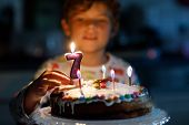 Adorable Happy Blond Little Kid Boy Celebrating His Birthday. Child Blowing Seven Candles On Homemad poster