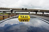Cab driving over a flyover, with a taxi sign on the rooftop of the car