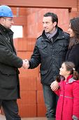 Architect shaking hands with a young family on site