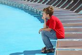 Tired boy sits on edge of deck-chair on blue deck of cruise liner