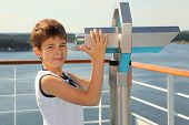 Boy stands on board of ship near big binoculars and looks at camera