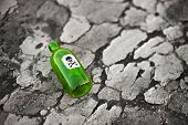 stock photo of scoria  - Bottle with the poison lying on poisoned ground - JPG