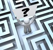 A man lost in a maze or labyrinth holds a question mark sign to seek help in finding a way out or ge
