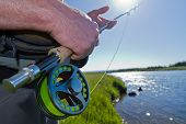 picture of fly rod  - A fisherman holding a fly rod and reel next to a river.