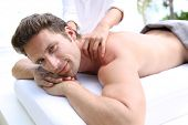 Handsome man laying on a massage bed