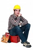 Young builder sitting on tool box
