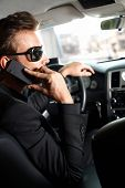Young man sitting in limousine, talking on cellphone.