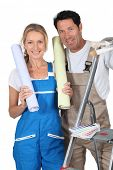 Man and woman with rolls of wallpaper and stepladder