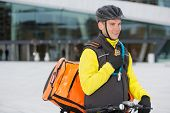Young male cyclist in protective gear with courier delivery bag using walkie-talkie