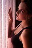 stock photo of blinders  - Beautiful young adult caucasian woman wearing a black top looking at the sunset through the blinders at her window - JPG