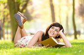 stock photo of storybook  - Happy woman reading and holding story book in fresh green park on spring or summer - JPG