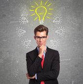 young business man has many idea lightbulbs surrounding his head