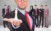 young business man leader of a successful business team holding the white king of chess on the top o