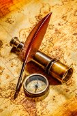 Vintage compass, goose quill pen, and spyglass lying on an old map.
