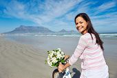 Woman with bicycle on beach in Cape Town, South Africa and Table Mountain