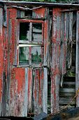 stock photo of 24th  - An old window surrounded by old wood and peeling red paint - JPG
