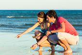Mann und Frau, Paar, genießen den romantischen Sonnenuntergang an einem Strand am Meer, in ihren Urlaub, sie