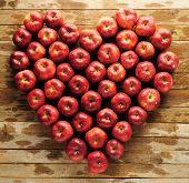 foto of assis  - Composizione a cuore di mele rosse adagiate su assi di legno - JPG