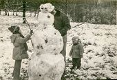 Vintage photo of father and daughters making a snowman (early eighties)
