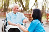 stock photo of wheelchair  - Kind doctor nurse outdoors taking care of an ill elderly woman in wheelchair - JPG