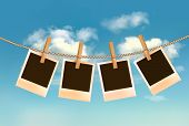 Retro photos hanging on a rope in front of a blue sky with clouds. Vector.