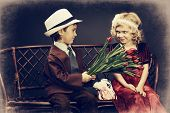 Cute little boy is giving bouquet of tulips to the charming little lady. Retro style.