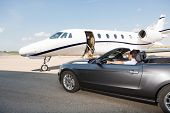 image of cabin crew  - Pilot in convertible parked against private jet at airport terminal - JPG