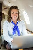 Portrait of beautiful airhostess with laptop sitting in private jet