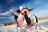 Friendly kids in winterwear riding on sledge outside