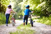 stock photo of 8-track  - Two Children Pushing Bikes Along Country Track - JPG